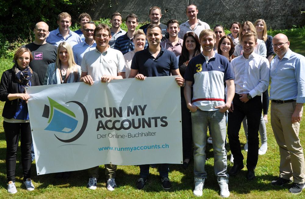 Run my Accounts Team Foto Wiese mit Plakat
